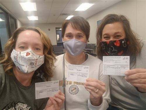 three masked nurses holding vaccination cards