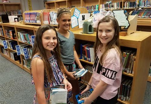 three middle school students in library